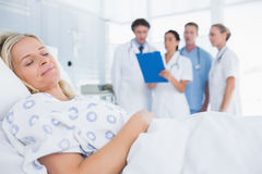 Sleeping patient with doctors behind Stock Image