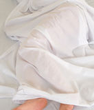 Sleeping person. Person covered with transparent white bed sheet Stock Photography