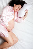 Sleeping pregnant woman in bed stock photo