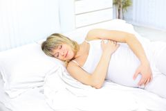 Sleeping pregnant woman on bed Royalty Free Stock Images