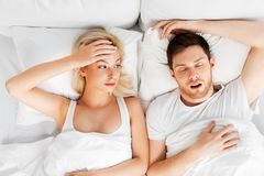 Unhappy woman in bed with snoring sleeping man. Sleeping problems and people concept - unhappy women lying in bed with snoring man royalty free stock photography
