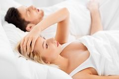 Unhappy woman in bed with snoring sleeping man. Sleeping problems and people concept - unhappy women lying in bed with snoring man stock image