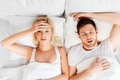 Unhappy woman in bed with snoring sleeping man. Sleeping problems and people concept - unhappy women lying in bed with snoring man stock photo