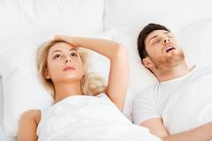 Unhappy woman in bed with snoring sleeping man stock image