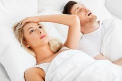Unhappy woman in bed with snoring sleeping man. Sleeping problems and people concept - unhappy women lying in bed with snoring man royalty free stock image