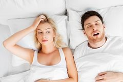 Unhappy woman in bed with snoring sleeping man stock photos