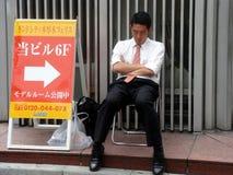 Sleeping salaryman. Overworked Japanese salaryman in suit sleeping on a chair in public Royalty Free Stock Image