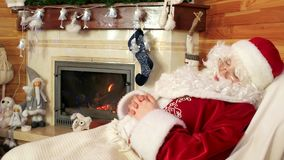 Sleeping sana claus, old tired santa snoozing after hard work, leisure time, room with fireplace stock footage