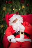 Sleeping Santa Clause on red Christmas armchair Stock Image