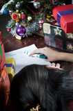 Sleeping on Santa's wish list. A view of a young teenage girl, surrounded by Christmas gifts and decorations, falls asleep while writing a wish list for Santa Stock Photo