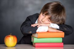 Sleeping school boy in classroom royalty free stock photography
