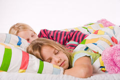 Sleeping sisters. Two young children enjoying their colorful bed royalty free stock images