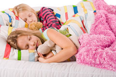 Sleeping sisters with bears. Two young children enjoying their colorful bed stock images