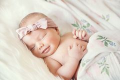 Sleeping smiling newborn baby in a wrap on white blanket. stock images
