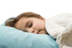 Sleeping Soundly. A little girl sleeping soundly in her bed, isolated against a white background Royalty Free Stock Photo