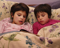 Sleeping through the Story. Mid-elementary child reading a story to her little sister, who has fallen asleep.  Both in nighties under the covers Royalty Free Stock Image