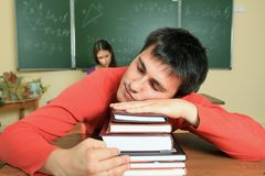 Sleeping student. Educational theme: male student in a classroom Royalty Free Stock Images