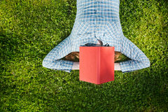 Sleeping Student. Education concept - female student lies on green grass with a red book over her head, top view Royalty Free Stock Photography