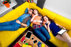 Sleeping and tired students on the couch. Sleeping and tired young students felt sleep after work on the yellow couch Royalty Free Stock Image