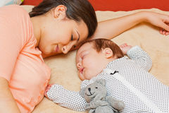 Sleeping together. Mother and baby quietly sleeping together on the bed Stock Image