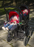 Sleeping twins baby in double stroller Stock Photos