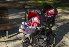 Sleeping twins baby in double stroller Stock Images