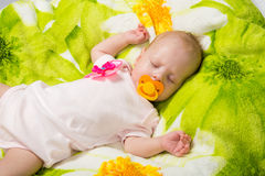 Sleeping two-month girl sucking a pacifier Stock Photo
