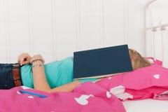 Sleeping under a school book Royalty Free Stock Photos