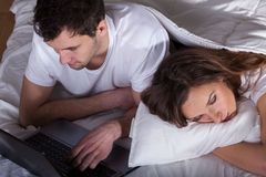 Sleeping wife and husband using computer Royalty Free Stock Images