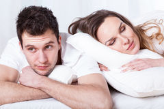 Sleeping wife and thoughtful husband Royalty Free Stock Photo