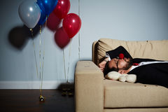 Sleeping after wild party. Waist-up portrait of bearded man with red clown nose sleeping on sofa after wild party, white bear lying under his head Stock Photo