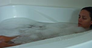 Woman asleep in bath. Sleeping woman in bathtub. She is relaxing in hot bath with bubbles stock video