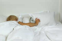 Sleeping Woman Covering Alarm Clock. With pillow which is showing she overslept the time Royalty Free Stock Photo
