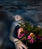 Sleeping woman in a dark water of a river Stock Images