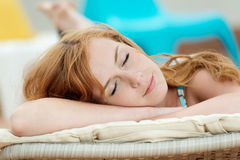 Sleeping Woman In Deck Chair. Portrait of a sleeping young woman in deck chair Royalty Free Stock Image