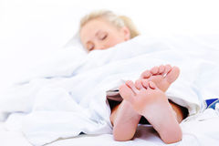 Sleeping woman with a feet on foreground royalty free stock photography