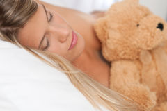 Sleeping woman holding brown teddy bear Stock Photography