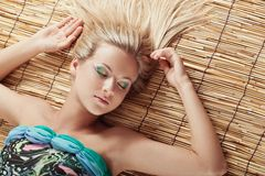 Sleeping woman laying on bamboo mat Stock Photo