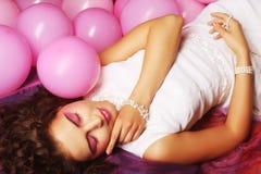 Sleeping woman lying on floor among balloons Royalty Free Stock Photography