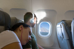 Sleeping woman lying on the male shoulder while he looking out t. Sleeping women lying on the male shoulder while he looking out the window of an flying airplane Stock Photos