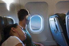 Sleeping woman lying on the male shoulder while traveling by air. Sleeping women lying on the male shoulder, both wearing headphones, while traveling by airplane Stock Photos