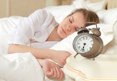 Sleeping woman resting in bed with alarm clock Stock Photos
