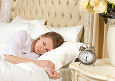 Sleeping woman resting in bed with alarm clock Stock Photo
