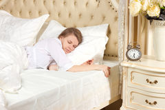 Sleeping woman resting in bed with alarm clock Royalty Free Stock Photo