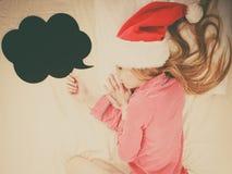 Sleeping woman wearing pajamas and Santa Claus hat. Sleeping woman waiting for Christmas season wearing pajamas and Santa Claus hat lying in bed dreaming about Royalty Free Stock Photos