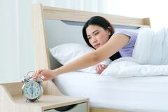 Free Sleeping Woman Wake Up In Early Morning Time At 6 AM And Her Hand Touching Off Alarm Clock In Bedroom Stock Image - 176994601