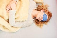 Sleeping woman wearing blindfold sleep mask. Tired woman sleeping in bed under blanket wearing blindfold sleep mask. Young girl taking nap Stock Image