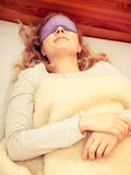 Sleeping woman wearing blindfold sleep mask. Tired woman sleeping in bed under blanket wearing blindfold sleep mask. Young girl taking nap. Instagram filter Stock Photo