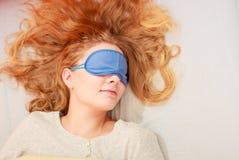 Sleeping woman wearing blindfold sleep mask. Tired woman sleeping in bed wearing blindfold sleep mask. Young girl taking nap Royalty Free Stock Photo