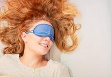 Sleeping woman wearing blindfold sleep mask. Tired woman sleeping in bed wearing blindfold sleep mask. Young girl taking nap Stock Photos
